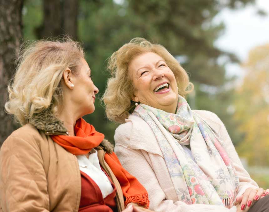 Women laughing on a park bench